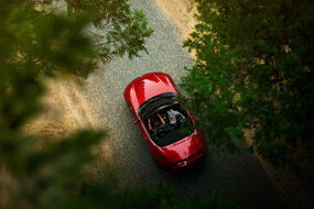 high up view of red Mazda Mx 5 Sport top down convertible through blurred trees on road