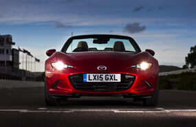 red Mazda Mx 5 Sport front view in evening with lights on