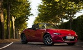 Mazda M X 5 sport side view red car on a tree lined road in the sun top down convertible nice