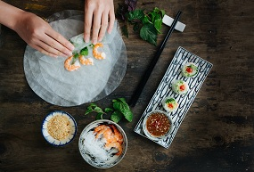 two hands making luxury sushi in a restaurant with prawns and rice