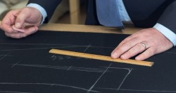 yorkshire tailor measuring fabric on a board